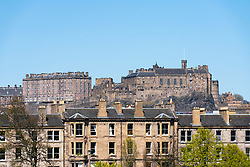 View of tenement apartment buildings overlooking  Bruntsfield Links in Edinburgh with Edinburgh Castle to rear, Scotland, UK