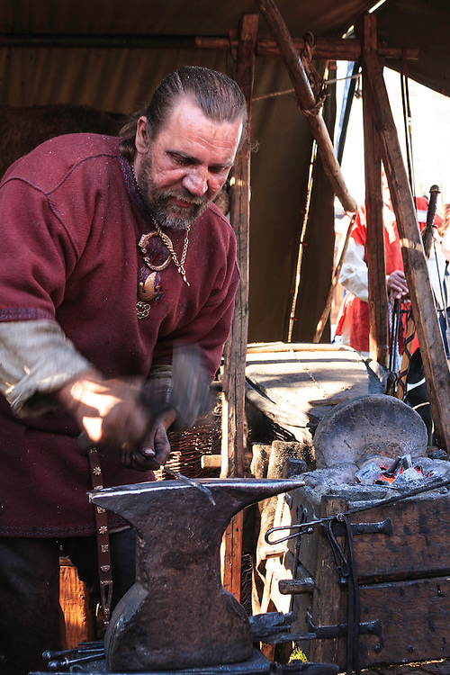 A blacksmith at work in Helsinki, Finland. The blacksmith makes his artisan products for sale at Helsinki summer market.