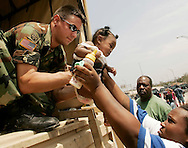 Heaven Girod who is five-months-old is handed over to a National Guardsman as she is being evacuated from a flooded area in New Orleans August 30, 2006.  Hurricane Katrina strengthened into a rare top-ranked storm and barrelled into the vulnerable U.S. Gulf Coast for a second and more deadly assault on the Gulf Coast.