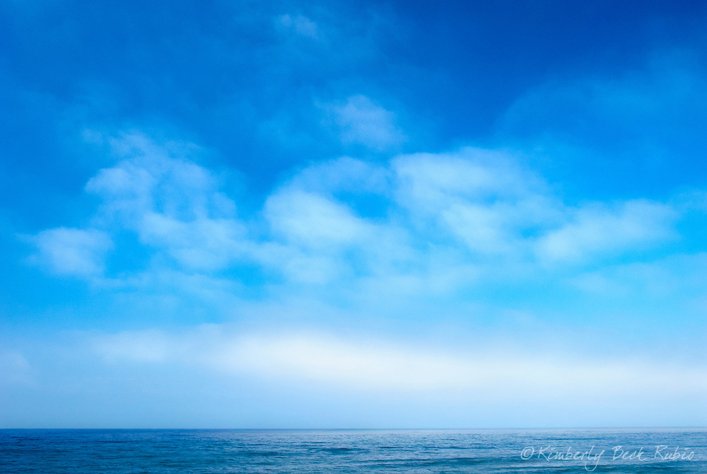 Cloudscape and fog bank dotting a blue sky over the ocean off the coast of La Jolla, California.
