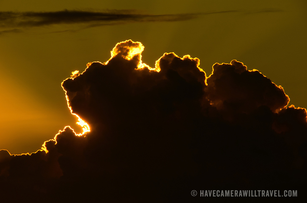 The setting sun illuminates the sharply defined edge of a cloud with golden light in the US Virgin Islands in the Caribbean.