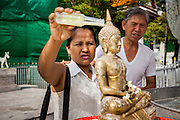 13 APRIL 2013 - BANGKOK, THAILAND: A couple bathes a statue of the Buddha with scented oils on Songkran in Bangkok. Songkran is the traditional Thai New Year's Festival. It is held April 13-16. Many Thais mark the holiday by going to temples and making merit by giving extra alms to monks or offering extra prayers. They also mark Songkran with joyous water fights. Songkran has been a national holiday since 1940, when Thailand moved the first day of the year to January 1.    PHOTO BY JACK KURTZ