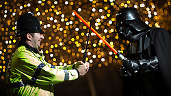 © Licensed to London News Pictures . 16/12/2015 . Manchester , UK . A policeman uses his extendable truncheon as a lightsabre in a duel with Darth Vadar . Star Wars fans attend the midnight screening of Star Wars the Force Awakens at the AMC Great Northern cinema in Manchester City Centre . Photo credit : Joel Goodman/LNP
