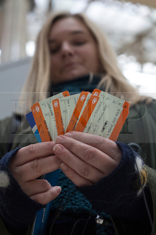 © licensed to London News Pictures. London, UK 28/11/2012. A passenger holding her train tickets after buying them from a ticket machine at Victoria Train Station. Rail fares set to increase by an average of 4.2% in January, a watchdog has revealed. Photo credit: Tolga Akmen/LNP
