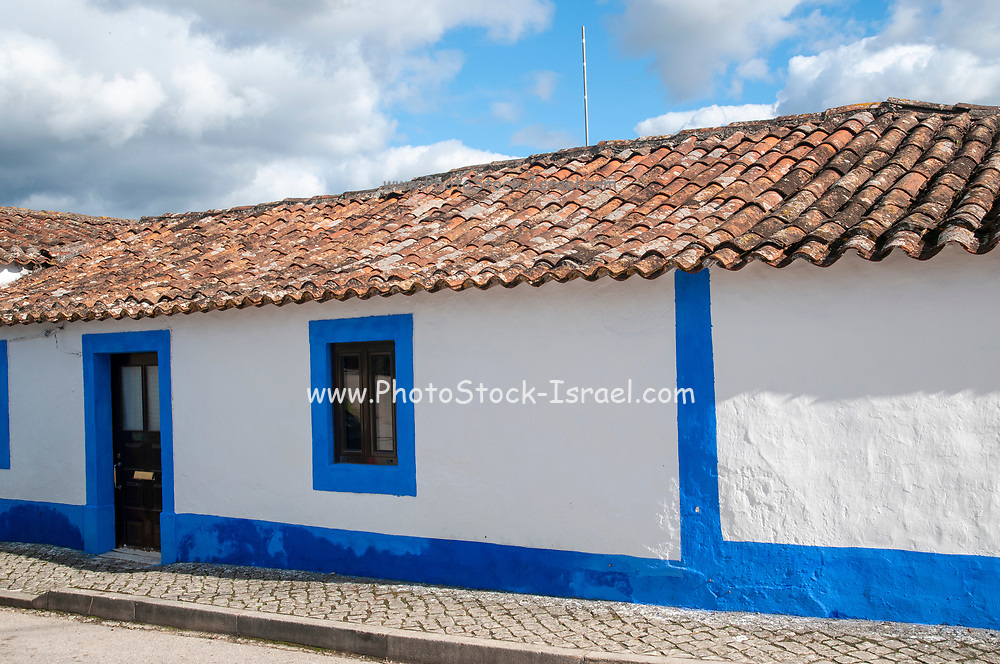Quaint blue and white houses line a street in a small Parish in the municipality of Obidos, Portugal