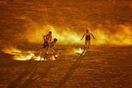 Children playing football at sunset on sandy ground, Ouarzazate, Morocco.