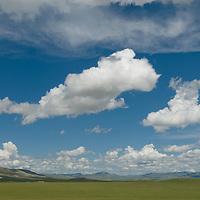 Summer cumulus clouds float above a Valley surrounding Lake Erkhel, near Muren, Mongolia.