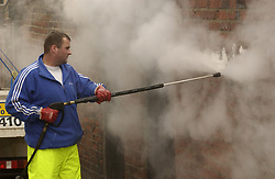 Council worker removing graffiti from wall with steam pressure hose; Tyneside UK