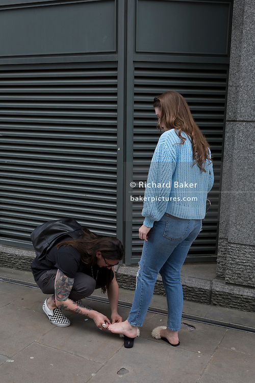 A man tends to the foot of a woman, on 17th April 2018, in the City of London, England.