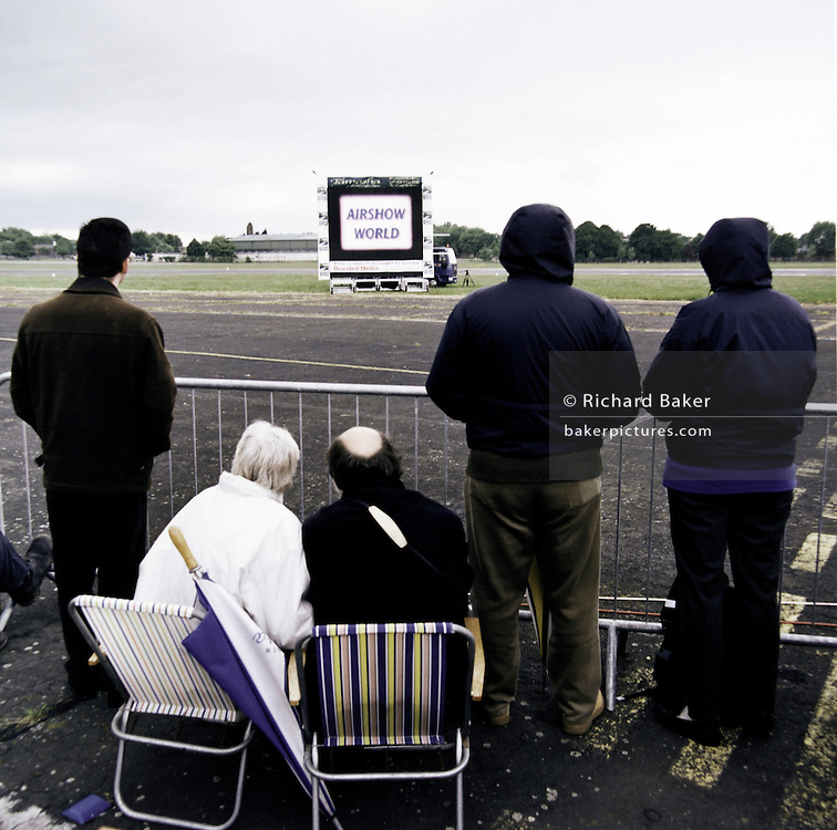 Waiting for the airshow to commence, an aviation enthusiast family huddle in the cold at Mildenhall, a US Air Force base in Suffolk, England.