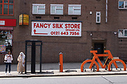 Old Fancy Silk Store sign on a wall near the city centre on 14th July 2021 in Birmingham, United Kingdom. The sign is part of recent additions to the street architecture here, with a giant orange bicycle rack on the pavement for cyclists to use.