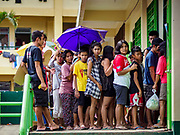29 JANUARY 2018 - GUINOBATAN, ALBAY, PHILIPPINES: People in line for the distribution of emergency supplies at the shelter for evacuees from Mayon volcano in Mauraro National High School in Guinobatan. There are 1,773 people in the shelter. Mayon volcano's eruptions continued Monday. At last count, more 80,000 people have been evacuated from their homes of the slopes of the volcano and are crowded into shelters in communities outside of the danger zone.    PHOTO BY JACK KURTZ
