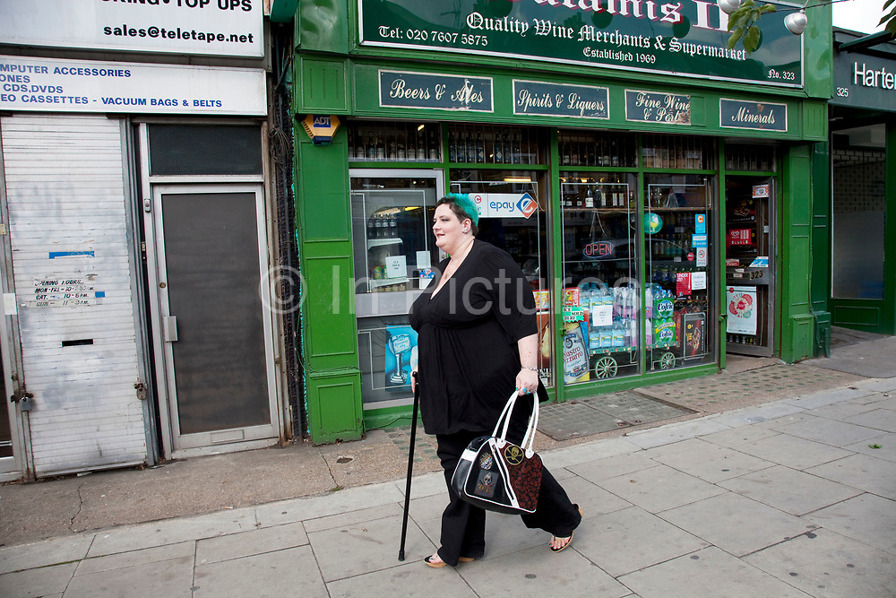 LONDON, ENGLAND, UK, JUNE 18TH 2011. Mother Louise Irwin-Ryan walking to the shops in her neighbourhood of Barnsbury, near to Kings Cross, North London. Louise is on various benefits to help support her family income, and housing, although recent government changed to benefits may affect her family drastically, possibly meaning they may have to move out of London. Louise Ryan was born on the Wirral peninsula in 1970.  She moved to London with her family in 1980.  Having lived in both Manchester and Ireland, she now lives permanently in North London with her husband and two children. Through the years Louise has battled to recover from a serious motorcycle accident in 1992 and has recently been diagnosed with Bipolar Affective Disorder. (Photo by Mike Kemp/For The Washington Post)