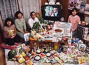 The Ukita family: Sayo Ukita, 51, and her husband, Kazuo Ukita, 53, with children Maya, 14 (holding chips) and Mio, 17 in their dining room in Kodaira City, Japan, with one week's worth of food. From the book Hungry Planet: What the World Eats (Model Released)