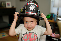 4 year old Max Gagnon proudly showed us his firemans helmet he received along with a video made by the Laconia Fire Department.  (Karen Bobotas/for the Laconia Daily Sun)