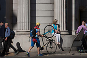 A cyclist pushes his upright bike on its rear wheel on the pavement at Bank station in the heart of Londons financial heart, on 15th August 2016 in the City of London, UK. Having upturned the bike to wheel it easily on the pavement, he steers it through the busy street where commuters walk beneath the pillars and columns of the Bank of England on Threadneedle Street.