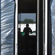 Nederland Zuid-Holland Zoetermeer  27-08-2009 20090827 Foto: David Rozing ..Serie over bouwsector. .Woningbouw, bouwvakker rust uit, leunt op reling in woning die in aanbouw is. Op de voorgrond isolatie materiaal. Worker taking a break, isolation materials. .Holland, The Netherlands, dutch, Pays Bas, Europe , staken, standaard perspectief, standaardperspectief, stilliggen, stop, stoppen, symbolisch, symbolische, techniek, technisch, technische, tele, telefoto, time out, tough, uitrusten, unrecognisable, van achteren gefotografeerd, veiligheidshelm, veiligheidskleding, vent, vermoeiend, voordeur, weinig voldoening, werk, werkgelegenheid, werkkleding, werknemer, werknemers, werkplek, werkterrrein, werkzaamheden, worker, workers, working class, working class.arbeid, zomers, zomerse dag, zonder inhoud, zonnig, zonnige, zwaar, zwaar beroep, zwaar werk, zware, zware beroepen