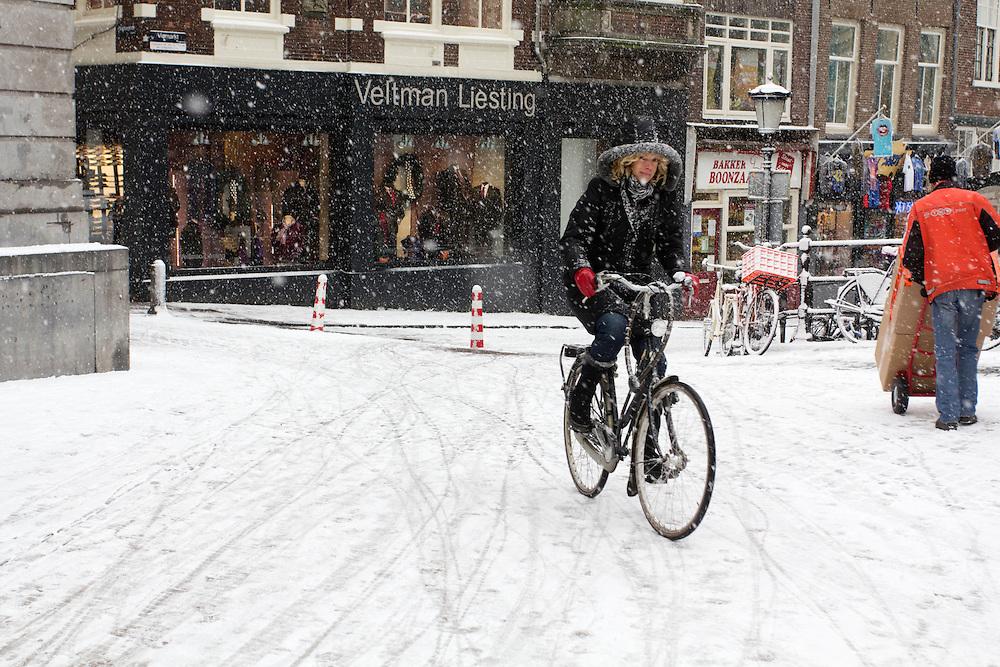 Een meisje fietst door de sneeuw over de Stadhuisbrug in Utrecht.<br /> <br /> A girl is cycling in the snow at the Stadhuisbrug in Utrecht.
