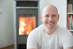 Portrait of man in his living room with fireplace, smiling