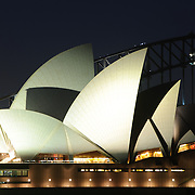 The famous Sydney Opera House and Sydney Harbour Bridge in the background as seen from rom Mrs. Macquarie's Point at night on Sydney Harbour, Australia.