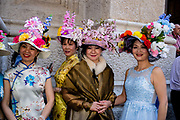 New York, NY - April 16, 2017. A group of Asian women in elaborate hats on the steps of St. Patrick's Cathedral at New York's annual Easter Bonnet Parade and Festival on Fifth Avenue.