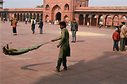 A young man sweeps the floor at the Jama Masjid Mosque, Old Delhi.