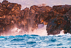 small sea arch in rugged lava rock formation at Kaiwi Point, at sunset, Kona Coast, Big Island, Hawaii, USA, Pacific Ocean