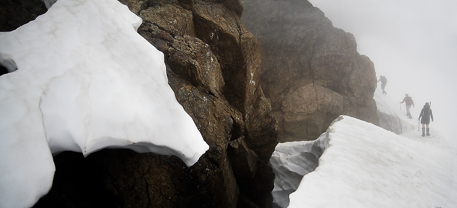 Three climbers climb a snow slope in the fog on an ascent of Tomyhoi Peak, Mount Baker Wilderness, Washington.