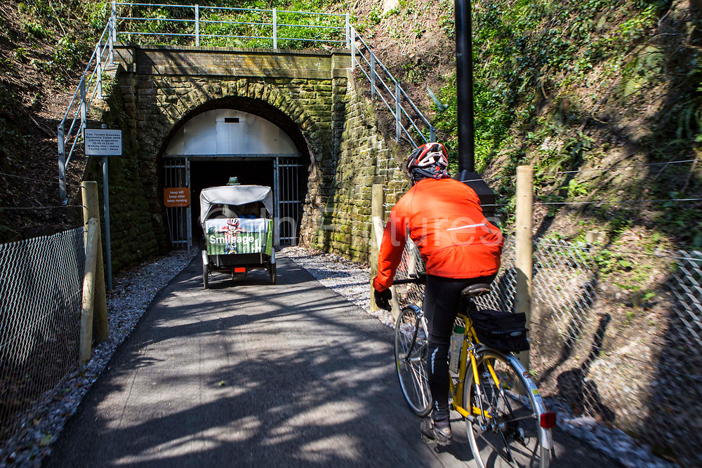 A Cyclist and a rickshaw approach the entrance to the restored Devonshire Tunnel which is part of the Two Tunnels Greenway near Bath, Somerset, England, United Kingdom on 6th April 2013.  The tunnel is 407 meters long and has been restored so it is accessible by foot, cycle or wheelchair and well light throughout.  The tunnel was previously part of a main railway line, the walls are blackened with a thick crust of soot from engine exhaust, while a strip in the roof is blasted clean by that same exhaust.  The tunnel is stone-lined throughout and on a curved and falling 1:50 gradient.  The tunnel is part of a 13-mile route and was restored by Sustrans in partnership with Bath and North East Somerset Council.  The opening of the route was attended by hundreds of cyclists and pedestrians to celebrate the new access to beautiful Somerset country-side.