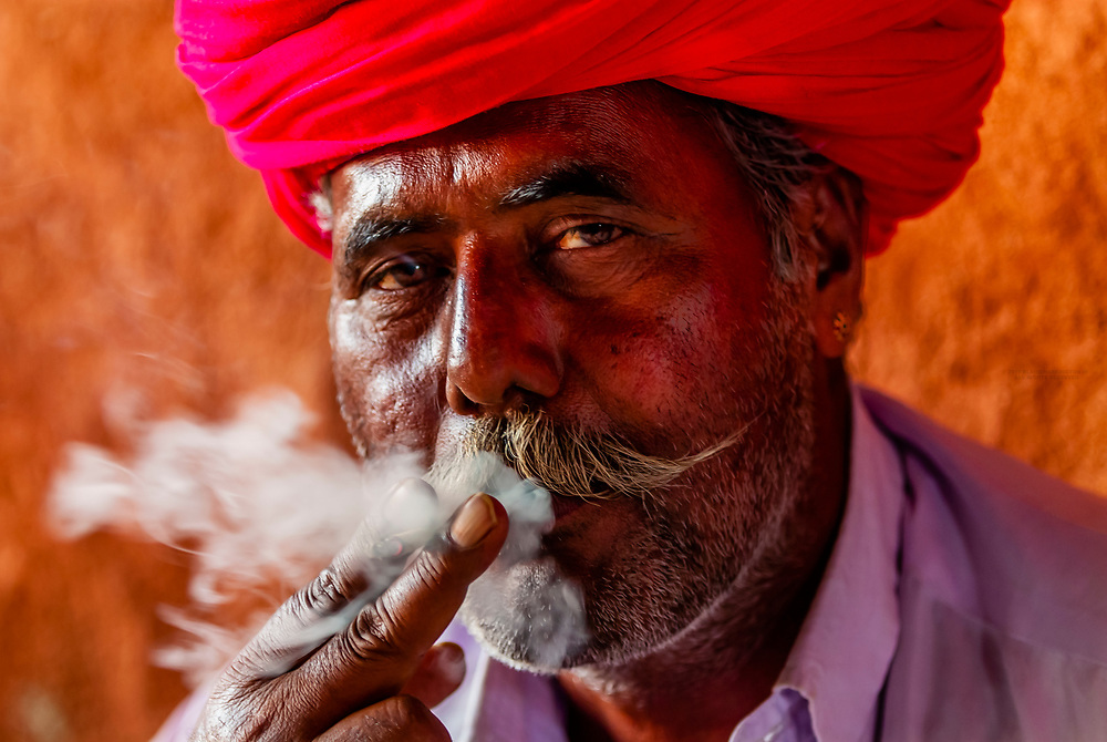 Man in Bishnoi tribal village smoking a bidi (clove cigarette) after an opium ceremony, near Rohet, Rajasthan, India