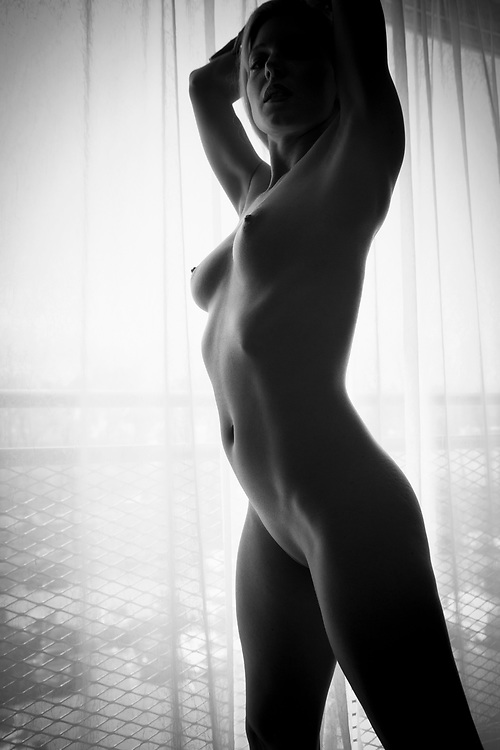Black and white of nude woman in front of window with her hands above her head