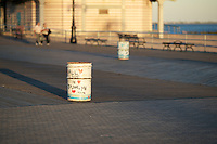 A garbage can on the boardwalk in Coney Island.