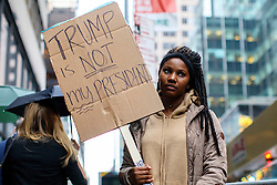 © Licensed to London News Pictures. 09/11/2016. New York CIty, USA. An anti-Trump campaigners protests outside Trump Tower in New York City, on Wednesday, 9 November 2016 following the presidential election won by Donald Trump. Photo credit: Tolga Akmen/LNP