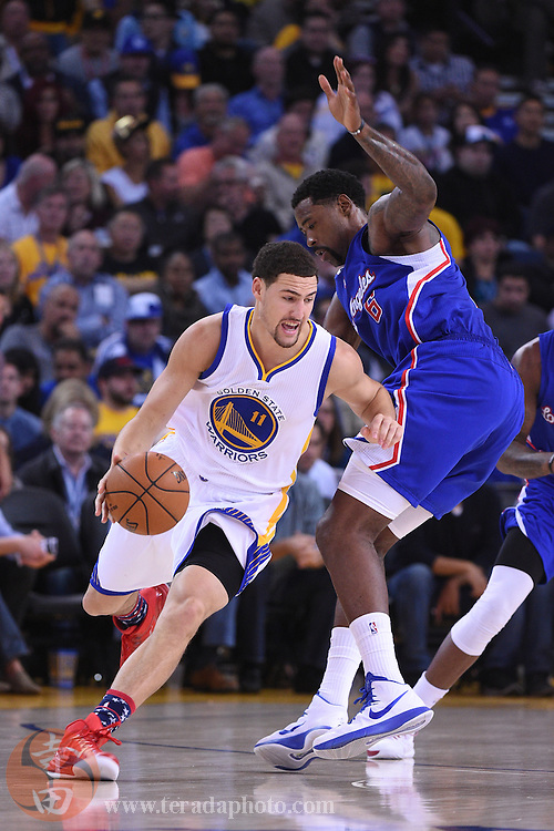 November 5, 2014; Oakland, CA, USA; Golden State Warriors guard Klay Thompson (11) dribbles the basketball against Los Angeles Clippers center DeAndre Jordan (6) during the second quarter at Oracle Arena. The Warriors defeated the Clippers 121-104.