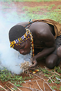 Hadzabe man blows on embers to start a fire. Photogrphed at Lake Eyasi, Tanzania