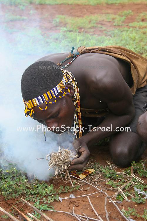 Hadzabe man blows on embers to start a fire. Photogrphed at Lake Eyasi, Tanzania