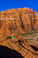 Woman hiking in the red rock formations of Snow Canyon State Park near St. George, Utah USA.
