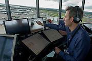 NATS Heathrow air traffic controller in control tower at Heathrow airport, London.