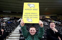 A young Derby County fan holds up a sign asking for the shirt of Ashley Cole before the Sky Bet Championship match at Pride Park, Derby.