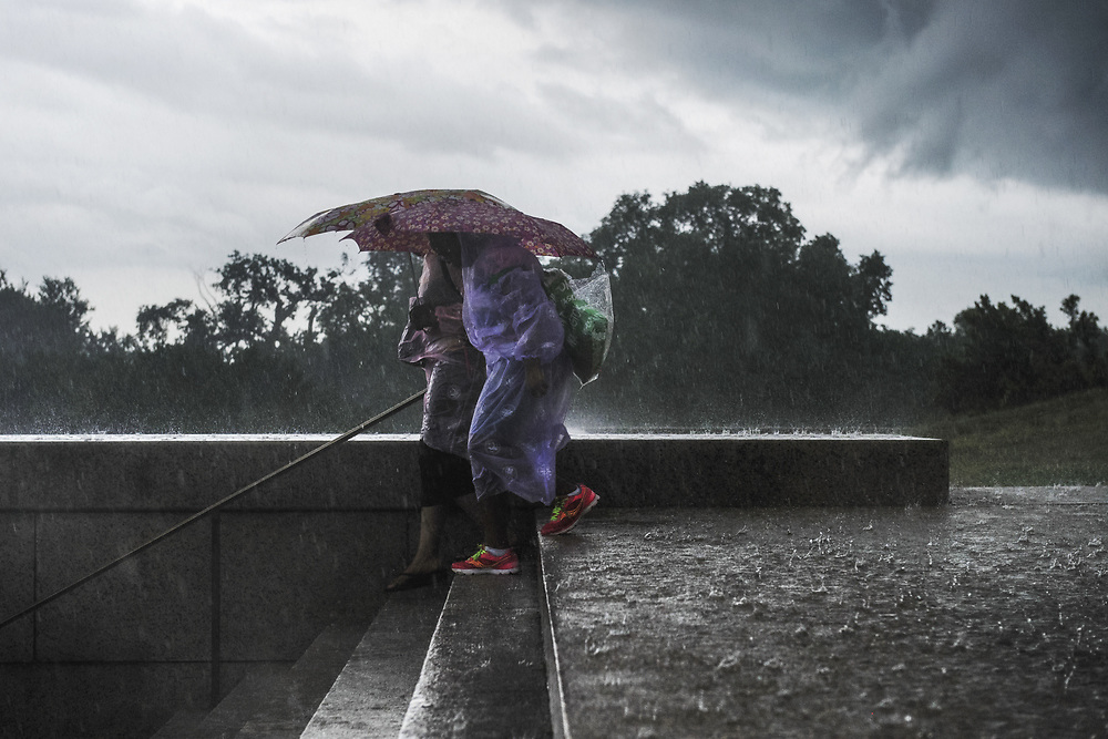 Two women descend the steps of the Lincoln memorial during a passing storm in Washington, D.C.