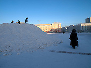 Children playing on a mountain of snow at a square in the city center of Yakutsk. Yakutsk is a city in the Russian Far East, located about 4 degrees (450 km) below the Arctic Circle. It is the capital of the Sakha (Yakutia) Republic (formerly the Yakut Autonomous Soviet Socialist Republic), Russia and a major port on the Lena River. Yakutsk is one of the coldest cities on earth, with winter temperatures averaging -40.9 degrees Celsius.