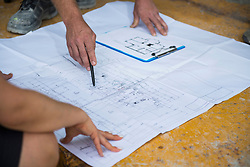 Architect discussing blueprint with construction worker at building site, Munich, Bavaria, Germany
