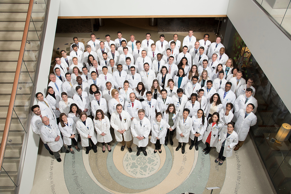 Faculty, fellows, and interns in the Department of General Surgery pose together in the atrium of the Duke Cancer Center