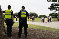 Police watch small groups of anti-lockdown protesters in a St Kilda park. After over 3 months of covid-19 lockdowns in Melbourne the easing of restrictions, allowed a small group of protesters to gather on St Kilda beach to protest police handing of demonstrations during the lock down. (Photo by Michael Currie/Speed Media)