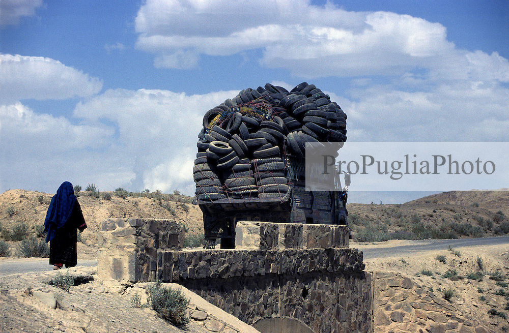 A truck loaded with second-hand tyres drives towards Khost and  woman wearing a blu burka walks by.