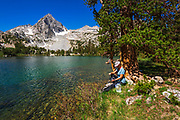 Hiker purifying water on the shore of Treasure Lake, John Muir Wilderness, Sierra Nevada Mountains, California USA