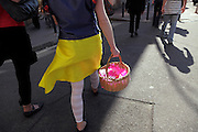 female person walking in bright skirt with little straw basket containing pink paper