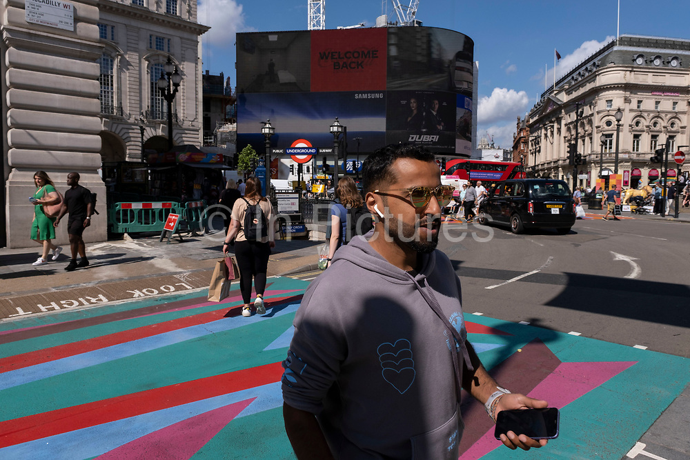 With many people and families staying in the UK for their Summer break during the school holidays, a large number of domestic tourists, who may normally have been travelling abroad, have decended on the capital to see the sights, as seen here in Piccadilly Circus as people cross the new graphic and patterned multi-coloured pedestrian crossings on 10th August 2021 in London, United Kingdom. Following the Coronavirus / Covid-19 health scare of the last two years, and with some travel restrictions still in place, more people have chosen a staycation which is a holiday spent in ones home country rather than abroad, or one spent at home and involving day trips to local attractions.
