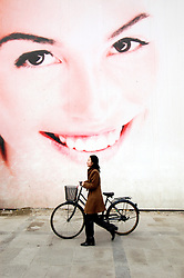 Woman pushes bicycle past large billboard of womans face advertising new property development in Beijing China
