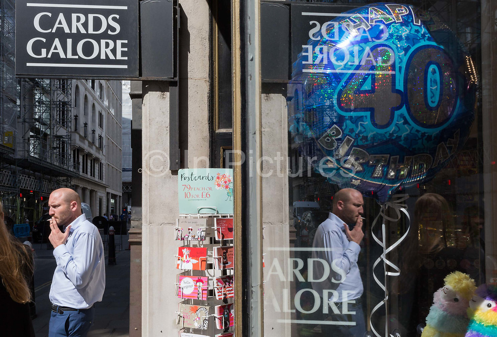 A man stands in sunshine smoking a cigarette in front of a shop selling party balloons including a large 40th birthday version, near Liverpool Street Station in the City of London, the capitals financial district - aka the Square Mile, on 8th August, in London, England.